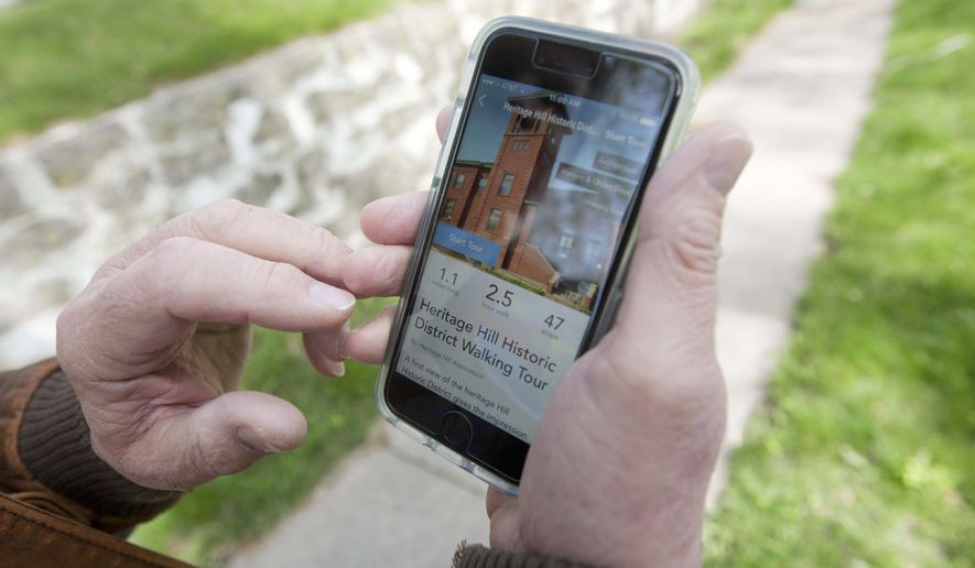 ADVANCE FOR SATURDAY MAY 13 AND THEREAFTER - In a Thursday, May 4, 2017 photo, Rodney Botts pulls up the PocketSights app with his phone near the corner of N. 7th Street and Columbia Streets in Burlington, Iowa. Burlington residents are encouraged to download the free app where they can start a walking tour of Heritage Hill Historic District, which was designed by Botts. (Ben Roberts/The Hawk Eye via AP)