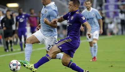 Orlando City's Donny Toia, right, tries to keep Sporting Kansas City's Roger Espinoza from advancing the ball during the first half of an MLS soccer game Saturday, May 13, 2017, in Orlando, Fla. (AP Photo/John Raoux)