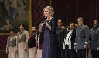 "Soprano Renee Fleming looks to the audience during the curtain call for Richard Strauss' opera ""Der Rosenkavalier"" in New York on Saturday, May 13, 2017. Fleming retired the role of the Marschallin on Saturday after 22 years. (Jonathan Tichler/Metropolitan Opera via AP)"