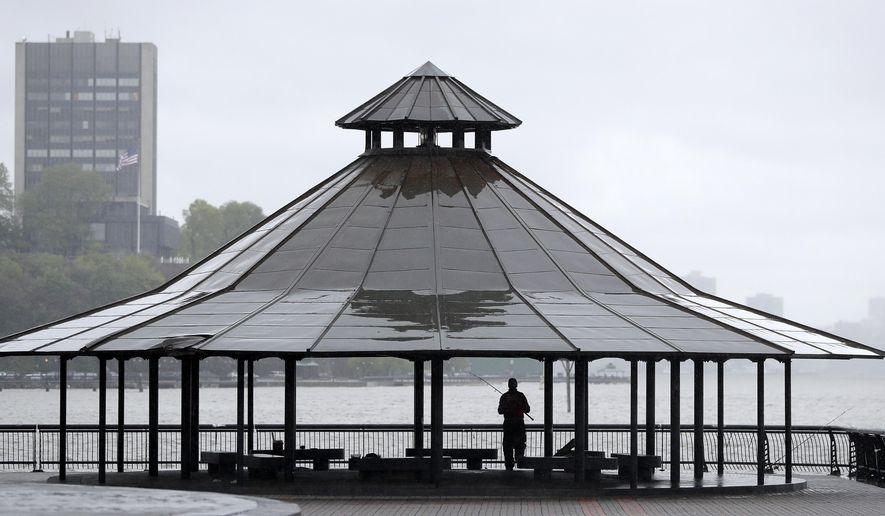 An angler takes shelter from the rain while fishing off Pier A Park, Saturday, May 13, 2017, in Hoboken, N.J. (AP Photo/Julio Cortez)
