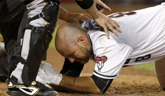 Arizona Diamondbacks' Chris Iannetta is attended to by Pittsburgh Pirates' Chris Stewart and umpire Ed Hickox after Iannetta was hit on the face with a pitch during the seventh inning of a baseball game Friday, May 12, 2017, in Phoenix. The Diamondbacks defeated the Pirates 11-4. (AP Photo/Ross D. Franklin)