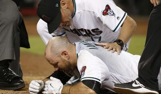 Arizona Diamondbacks' Chris Iannetta, bottom, is attended to by manager Torey Lovullo, top, after Iannetta was hit on the face with a pitch by Pittsburgh Pirates' Johnny Barbato during the seventh inning of a baseball game Friday, May 12, 2017, in Phoenix. The Diamondbacks defeated the Pirates 11-4. (AP Photo/Ross D. Franklin)