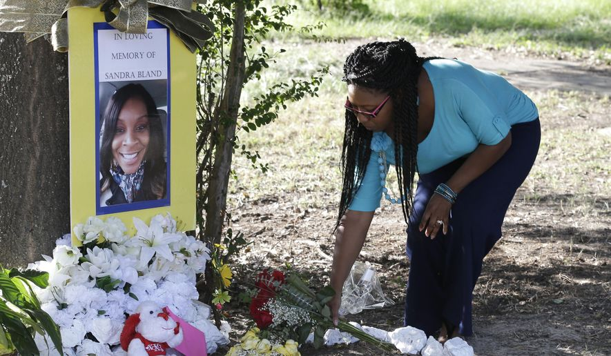 "FILE - In this July 21, 2015 photo, Jeanette Williams places a bouquet of roses at a memorial for Sandra Bland near Prairie View A&M University, in Prairie View, Texas. The sister of Sandra Bland, a black woman found dead in a Texas jail following a confrontational traffic stop with a white state trooper, says it is ""gut-wrenching"" that lawmakers stripped police reforms from a bill named after her sibling and are now pushing a weakened compromise that ""painfully misses the mark."" (AP Photo/Pat Sullivan, File)"