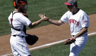 San Francisco Giants catcher Nick Hundley, left, celebrates with pitcher Derek Law after the final out of the ninth inning of a baseball game against the Cincinnati Reds in San Francisco, Saturday, May 13, 2017. (AP Photo/Jeff Chiu)