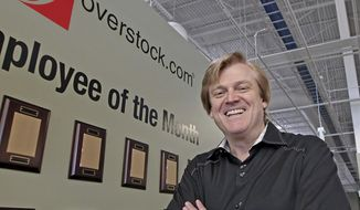 his March 25, 2010, file photo, Chairman and CEO of OverStock.com Patrick Byrne poses for a picture by the employee of the month wall at the warehouse of Overstock.com outside of Salt Lake City, Utah. (AP Photo/George Frey, file)