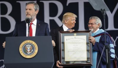 President Donald Trump, center, is presented an Honorary Degree by Ronald E. Hawkins, right, Provost and Chief Academic Officer, before giving the commencement address for the Class of 2017 at Liberty University in Lynchburg, Va., Saturday, May 13, 2017. Speaking at the podium is Liberty University President Jerry Falwell, left. (AP Photo/Pablo Martinez Monsivais)