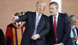 President Donald Trump gestures as he stands with Liberty University president, Jerry Falwell Jr., right, during commencement ceremonies at the school in Lynchburg, Va., Saturday, May 13, 2017. (AP Photo/Steve Helber) ** FILE **