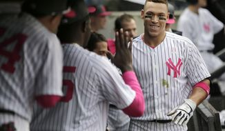 New York Yankees' Aaron Judge is greeted in the dugout after hitting a solo home run during the fourth inning of a baseball game against the Houston Astros, Sunday, May 14, 2017, in New York. (AP Photo/Seth Wenig)