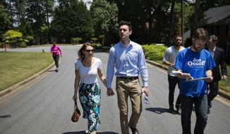 Jon Ossoff, center, a 30-year-old Democrat running for Congress in Georgia's traditionally conservative 6th Congressional District, and fiancee Alisha Kramer, left, walk with organizer Eliot Beckham, right, while campaigning in Sandy Springs, Ga., Thursday, May 11, 2017. (AP Photo/David Goldman) ** FILE **