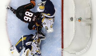 Nashville Predators' Mattias Ekholm (14) collides with Anaheim Ducks' Ondrej Kase (86) as they battle for the puck by the goal during the first period of Game 2 of the Western Conference final in the NHL hockey Stanley Cup playoffs, Sunday, May 14, 2017, in Anaheim, Calif. (AP Photo/Chris Carlson)