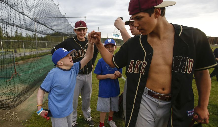 ADVANCE FOR USE SUNDAY, MAY 14 - In this May 4, 2017 photo, Matthew and Noah Irish look on as Lakewood High School baseball player Morgan Stacey fist-bumps with Jacob Irish as all players leave the fields due to an incoming lightning storm in Marysville, Wash. Affected by life-threatening Hurler syndrome since birth, Jacob is playing this season on a Stilly Valley Little League Challenger Division team (Dan Bates/The Herald via AP)