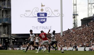 Tottenham's Victor Wanyama, right, vies for the ball with Manchester United's Michael Carrick below a display screen during the English Premier League soccer match between Tottenham Hotspur and Manchester United at White Hart Lane stadium in London, Sunday, May 14, 2017. It is the last Spurs match at the old stadium, a new stadium is being built on the site. (AP Photo/Frank Augstein)