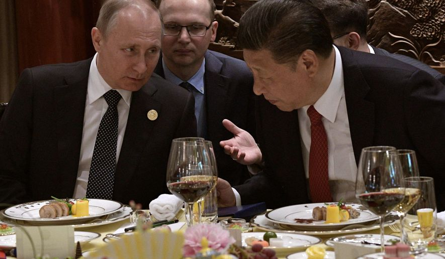 Russian President Vladimir Putin, left, and Chinese President Xi Jinping chat during a breakfast prior to the opening ceremony of the Belt and Road Forum in Beijing, Sunday, May 14, 2017. (Alexei Nikolsky, Sputnik, Kremlin Pool Photo via AP)