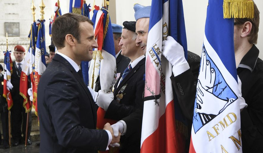 French President Emmanuel Macron greets veterans at the the Unknown Soldier's tomb under the Arc de Triomphe after his formal inauguration ceremony as French President Sunday, May 14, 2017 in Paris. Macron was inaugurated as France's new president at the Elysee Palace in Paris, and immediately launched into his mission to shake up French politics, world economics and the European Union. (Alain Jocard, Pool via AP)