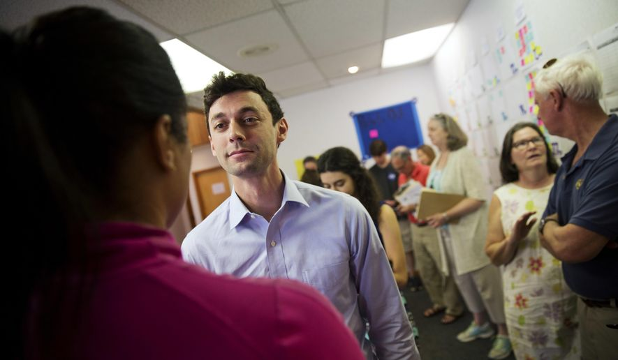 Volunteer Veronica Savoy, left, talks with Jon Ossoff, a 30-year-old Democrat running for Congress in Georgia's traditionally conservative 6th Congressional District at his campaign office in Sandy Springs, Ga., Thursday, May 11, 2017. Ossoff's fortunes in a June 20 matchup with Republican Karen Handel will be an early test of how the Republicans' vote to gut the Affordable Care Act and President Donald Trump's decision to fire the FBI director are playing with voters. Both parties see the Georgia race as an indicator for the 2018 midterm elections. (AP Photo/David Goldman)