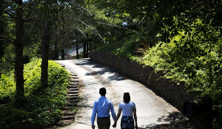 Jon Ossoff, left, a 30-year-old Democrat running for Congress in Georgia's traditionally conservative 6th Congressional District, and fiancee Alisha Kramer, walk up a driveway to knock on a door while campaigning in Sandy Springs, Ga., Thursday, May 11, 2017. Ossoff's fortunes in a June 20 matchup with Republican Karen Handel will be an early test of how the Republicans' vote to gut the Affordable Care Act and President Donald Trump's decision to fire the FBI director are playing with voters. Both parties see the Georgia race as an indicator for the 2018 midterm elections. (AP Photo/David Goldman)