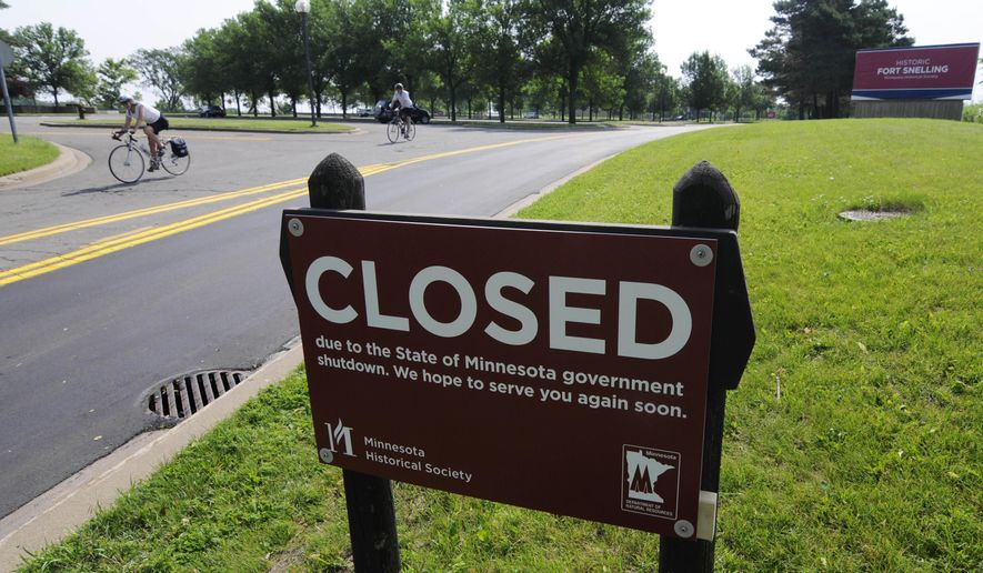FILE - In this July 1, 2017, file photo, bicyclists ride on the road leading out of the closed Fort Snelling historic site in Minneapolis after negotiations over the state budget between Republican lawmakers and Democratic Gov. Mark Dayton broke down and the government shutdown at midnight. Minnesota's political leaders are entering the legislative homestretch with no budget deal in sight. It's familiar territory. Democratic Gov. Mark Dayton and the Republican-controlled Legislature have until the May 22, 2017, deadline to finish the budget. (AP Photo/Jim Mone, File)