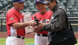 FILE - In this March 6, 2006, file photo, Team USA coach John McLaren, left, presents supervisor of umpires Steve Palermo, right, with a statue he bought with Palermo in mind several years ago in Venezuela, as manager Buck Martinez, center, looks on during practice in Phoenix. Former big league umpire Palermo, whose accomplished career ended when he was shot trying to break up a robbery in 1991, has died. He was 67. (AP Photo/Paul Connors, File)