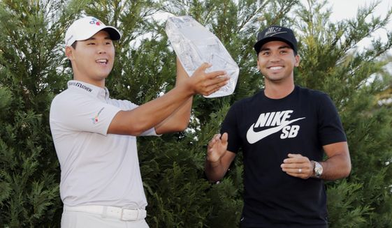 Si Woo Kim of South Korea, holds The Players Championship Trophy, Sunday, May 14, 2017, in Ponte Vedra Beach, Fla. To the right is Jason Day who won the tournament last year. (AP Photo/Lynne Sladky)