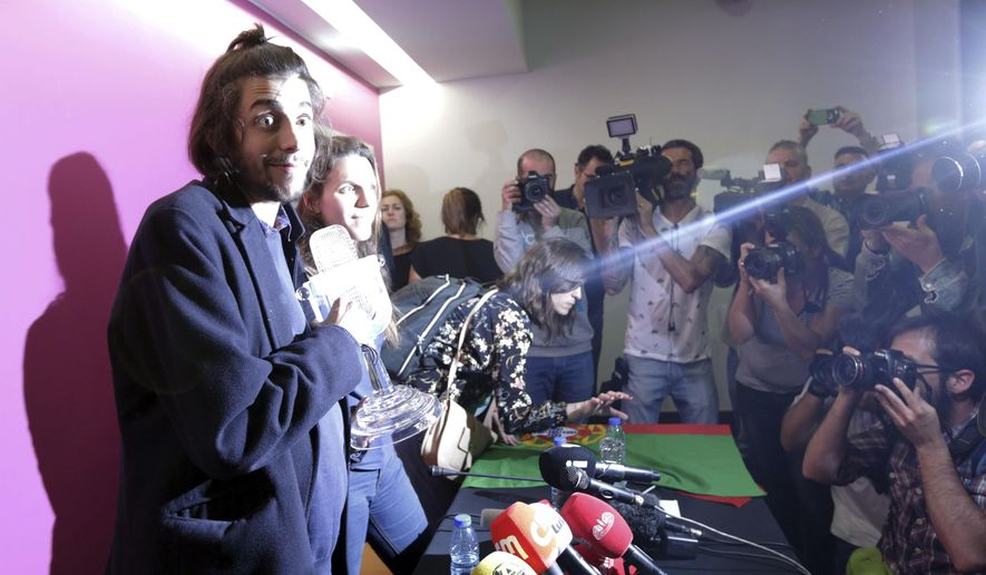 """Salvador Sobral, left, and his sister Luisa Sobral, are lit by a camera flash, as they arrive for a news conference holding the Eurovision award, at the Lisbon airport, Sunday, May 14 2017, after winning the Final of the Eurovision Song Contest with his song """"Amar pelos dois"""", in Kiev, Ukraine, Saturday. (AP Photo/Armando Franca)"""