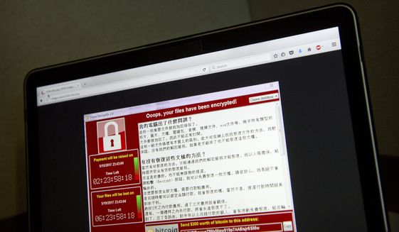 In this May 13, 2017, file photo, a screenshot of the warning screen from a purported ransomware attack, as captured by a computer user in Taiwan, is seen on laptop in Beijing. (AP Photo/Mark Schiefelbein, File)