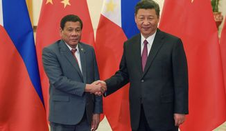 Philippine President Rodrigo Duterte, left, and Chinese President Xi Jinping pose for photographers prior to their bilateral meeting held on the sidelines of the Belt and Road Forum for International Cooperation at the Great Hall of the People in Beijing, Monday, May 15, 2017. (Etienne Oliveau/Pool Photo via AP)