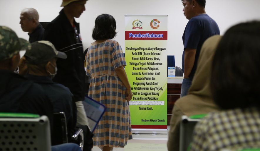 "Patients wait near a banner informing about the delay in service put up at the registration desks at Dharmais Cancer Hospital in Jakarta, Indonesia, Monday, May 15, 2017. Dozens of the hospital's computer were hit by the global ""ransomware"" cyberattack on Saturday causing disruption to services and making patients had to wait longer while staff had to work with paper records. Writings on the banner read: ""Currently there is a trouble on the hospital's information system caused by virus. We apologize to patients and visitors for the inconvenience caused. The problem is being resolved at the moment."" (AP Photo/Dita Alangkara)"
