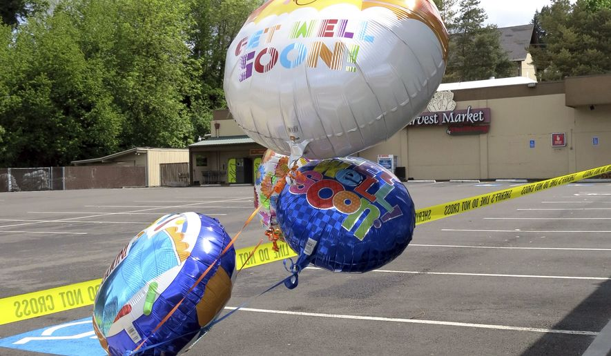Well-wishing balloons for an injured employee float behind police tape outside a grocery store in Estacada, Ore., Monday, May 15, 2017. Police say a man carrying what appeared to be a human head stabbed an employee at the grocery store. (AP Photo/Gillian Flaccus)