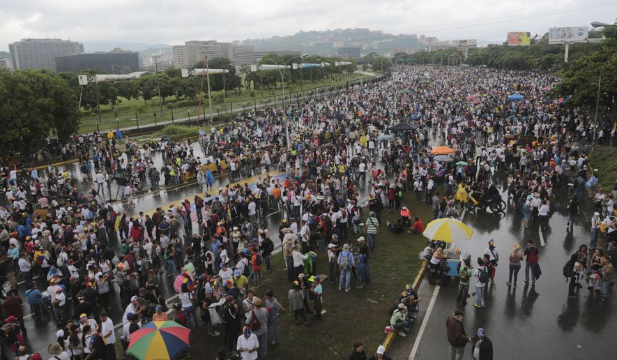 People gather on a highway for a national sit-in against President Nicolas Maduro, in Caracas, Venezuela, Monday, May 15, 2017. Opposition leaders are demanding immediate presidential elections. (AP Photo/Fernando Llano)
