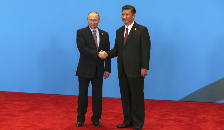 Chinese President Xi Jinping, right, shakes hands with Russian President Vladimir Putin as they attend the welcome ceremony at Yanqi Lake during the Belt and Road Forum, in Beijing, China, Monday, May 15, 2017. (Roman Pilipey/Pool Photo via AP)