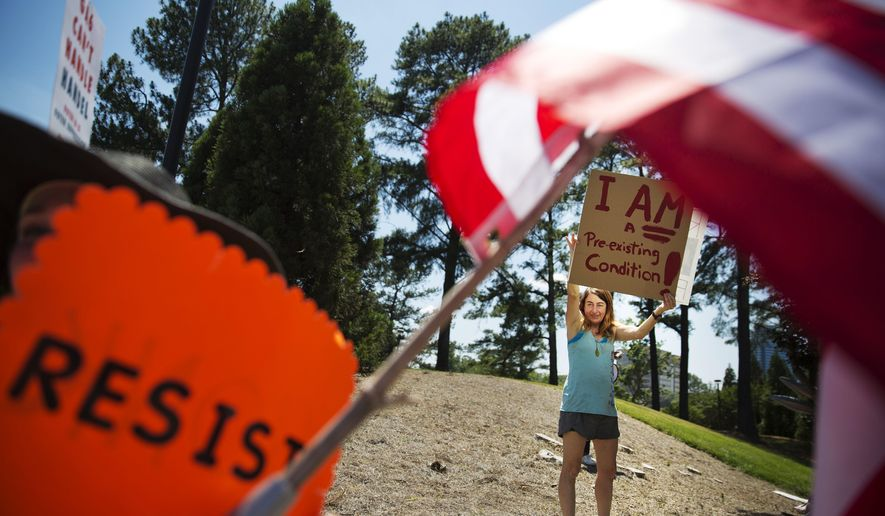 Jennifer Thompson protests a scheduled visit by House Speaker Paul Ryan at a campaign event for Republican candidate for 6th congressional district Karen Handel in Dunwoody, Ga., Monday, May 15, 2017. (AP Photo/David Goldman)