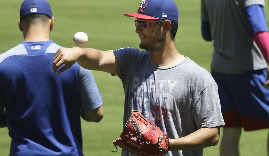 Texas Rangers pitcher Yu Darvish, of Japan, tosses a ball around in the outfield during batting practice before a baseball game against the Oakland Athletics in Arlington, Texas, Sunday, May 14, 2017. (AP Photo/LM Otero)