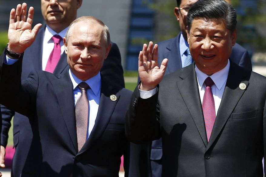 Chinese President Xi Jinping, right, and Russian President Vladimir Putin wave as leaders pose for a family photo during the Belt and Road Forum at meeting's venue on Yanqi Lake just outside Beijing, China, Monday, May 15, 2017. (Damir Sagolj/Pool Photo via AP)