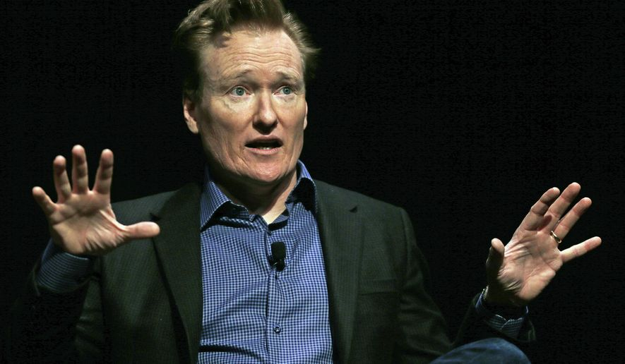 In this Feb. 12, 2016 file photo television host Conan O'Brien gestures to the audience at Sanders Theatre on the campus of Harvard University in Cambridge. (AP Photo/Charles Krupa,File)