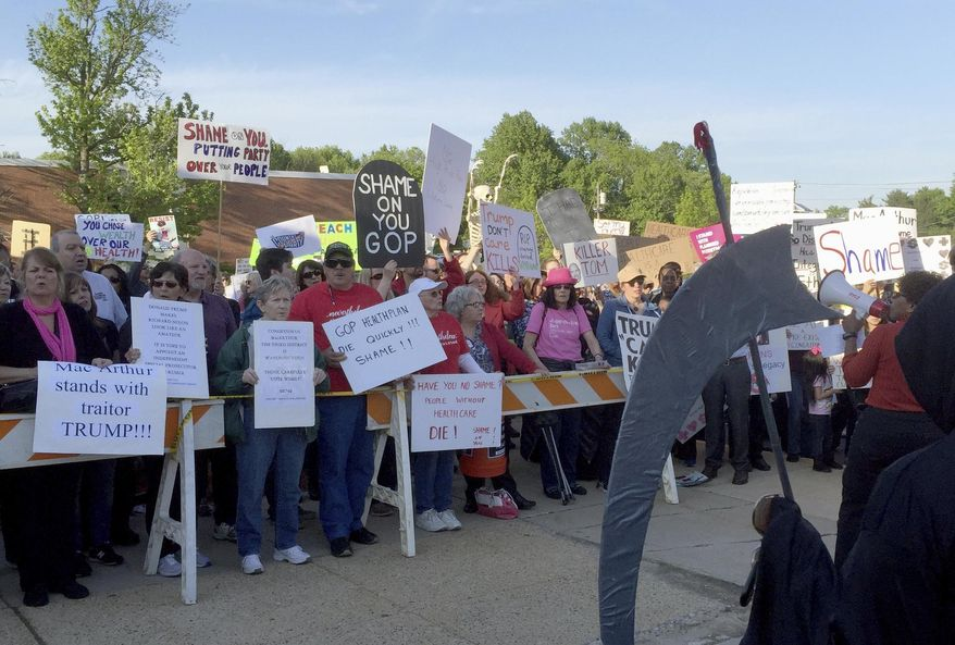 In this Wednesday, May 10, 2017 file photo, protesters rally outside the town hall held by New Jersey Republican Rep. Tom MacArthur in Willingboro, N.J. Americans vented some frustrations this past week in Republican districts crucial to GOP majority control of the House, sounding off about health care and President Donald Trump's abrupt firing of FBI Director James Comey. Republicans in some districts faced a backlash over their votes for the House health care bill at raucous town halls, with plenty of complaints about a provision that would allow insurers to charge seriously ill customers higher rates if they let their coverage lapse. Other lawmakers avoided holding forums. (AP Photo/Michael Catalini)