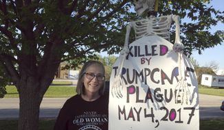 In this May 11, 2017 photo, Jeannie Scown protests outside U.S. Rep. Randy Hultgren's office in McHenry, Ill. Scown, a retired teacher from Geneva Ill., was part of a group of about 30 people who demonstrated against Hultgren's health care vote. (AP Photo/Sara Burnett)