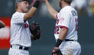 Colorado Rockies shortstop Pat Valaika, left, is congratulated by first baseman Mark Reynolds after they retired the Los Angeles Dodgers in the ninth inning of a baseball game Sunday, May 14, 2017, in Denver. (AP Photo/David Zalubowski)