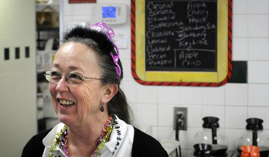 """In this April 21, 2017 photo, Connie Suprenant, wearing a tiara that says, """"Retired"""" smiles  as a customer at the Blues Cafe in Kankakee wishes her well in retirement. After 40 years, with pitcher of water in one hand and iced tea in the other, on Suprenant's last day, the restaurant was busy, with customers coming in to say goodbye, and to leave balloons and flowers. (Mike Voss/The Daily Journal via AP)"""