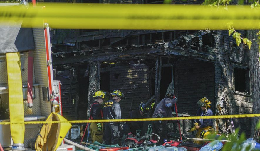 Firefighters investigate the remains of a burned home in Akron, Ohio on Monday, May 15, 2017. Firefighters said multiple people died in the fire at the home. (AP photo/Dake Kang)