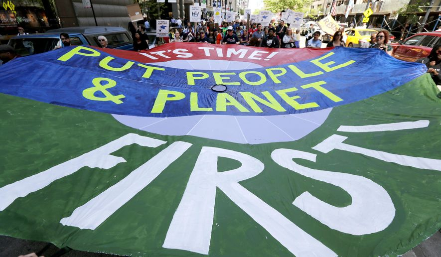 Protesters march with a large parachute banner during the beginning of a march to Springfield, Ill., protesting the state's budget crisis Monday, May 15, 2017, in Chicago. Organizers say the 200 mile trip is scheduled to take 15 days with about 100 people going the distance. (AP Photo/Charles Rex Arbogast)