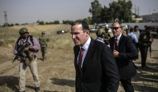 """Brett McGurk, center, the special presidential envoy for the global coalition against the Islamic State visits water treatment plant south of Mosul on Monday, May 15, 2017.  The senior U.S. official says the fight to retake Mosul from the Islamic State group is approaching its """"final stages."""" (AP Photo/Bram Janssen)"""