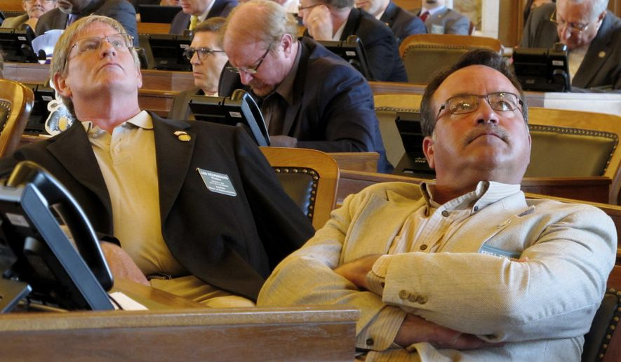 Kansas state Reps. Leo Delperdang, left, R-Wichita, and Kent Thompson, R-Iola, watch as the House approves a bill raising new revenue by eliminating exemptions to the state's sales tax, Monday, May 15, 2017, at the Statehouse in Topeka, Kan. The bill imposes the tax on a few services that have not been taxed, and both lawmakers support it. (AP Photo/John Hanna)