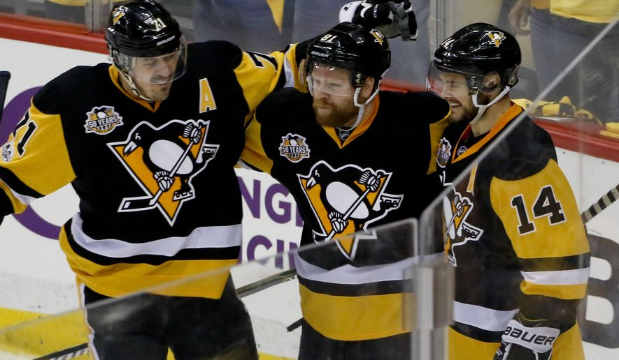Pittsburgh Penguins' Phil Kessel, center, celebrates with teammates Evgeni Malkin (71) and Chris Kunitz (14) after scoring against the Ottawa Senators during the third period of Game 2 of the Eastern Conference final in the NHL hockey Stanley Cup playoffs, Monday, May 15, 2017, in Pittsburgh. (AP Photo/Gene J.Puskar)