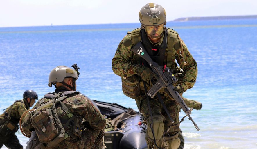 FILE - In this May 13, 2017 file photo, Japanese soldiers use rubber rafts as part of an amphibious drill during joint military exercises between the U.S., Japan, France and U.K. on Naval Base Guam. U.S. marines joined with forces from Japan, France and Britain for live-firing exercises on the American territory of Guam that are intended to show support for the free passage of vessels in international waters amid concerns China may restrict access to the South China Sea. (AP Photo/Haven Daley, File)