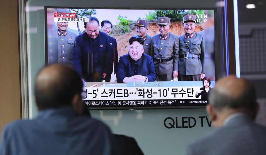 """People watch a TV news program showing an image of North Korean leader Kim Jong Un, published in the country's Rodong Sinmun newspaper, at Seoul Railway station in Seoul, South Korea, Monday, May 15, 2017. North Korea said Monday the missile it launched over the weekend was a new type of """"medium long-range"""" ballistic rocket that can carry a heavy nuclear warhead. A jubilant leader Kim Jong Un promised more nuclear and missile tests and warned that North Korean weapons could strike the U.S. mainland and Pacific holdings. (AP Photo/Lee Jin-man)"""