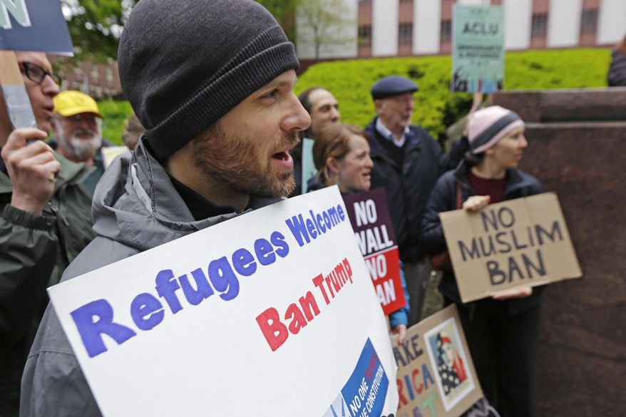 """Miles Treakle, left, of Seattle, holds a sign that reads """"Refugees Welcome Ban Trump,"""" as he protests against President Donald Trump's revised travel ban, Monday, May 15, 2017, outside a federal courthouse in Seattle. A three-judge panel of the 9th U.S. Circuit Court of Appeals heard arguments Monday in Seattle over Hawaii's lawsuit challenging the travel ban, which would suspend the nation's refugee program and temporarily bar new visas for citizens of Iran, Libya, Somalia, Sudan, Syria and Yemen. (AP Photo/Ted S. Warren)"""