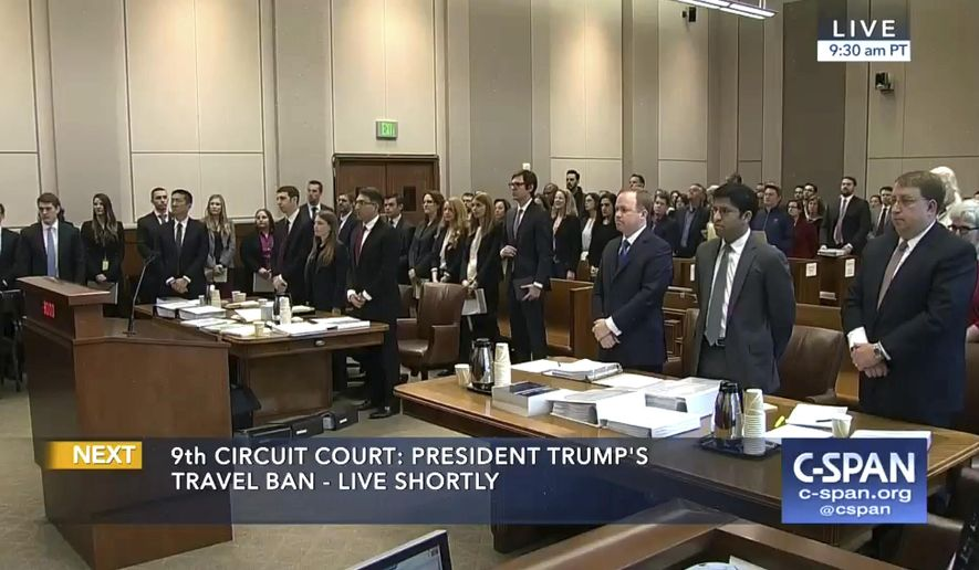 In this image made from a C-SPAN video, participants and members in the gallery stand as three judges for the 9th US Circuit Court of Appeals enter the room in Seattle, Monday, May 15, 2017. The panel is hearing arguments over Hawaii's lawsuit challenging the travel ban, which would suspend the nation's refugee program and temporarily bar new visas for citizens of Iran, Libya, Somalia, Sudan, Syria and Yemen. (CSPAN via AP, Pool)