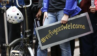 "A protester holds a poster with the social media hashtag ""#refugeesWelcome,"" during a demonstration against President Donald Trump's revised travel ban, Monday, May 15, 2017, outside a federal courthouse in Seattle. A three-judge panel of the 9th U.S. Circuit Court of Appeals heard arguments Monday in Seattle over Hawaii's lawsuit challenging the travel ban, which would suspend the nation's refugee program and temporarily bar new visas for citizens of Iran, Libya, Somalia, Sudan, Syria and Yemen. (AP Photo/Ted S. Warren)"