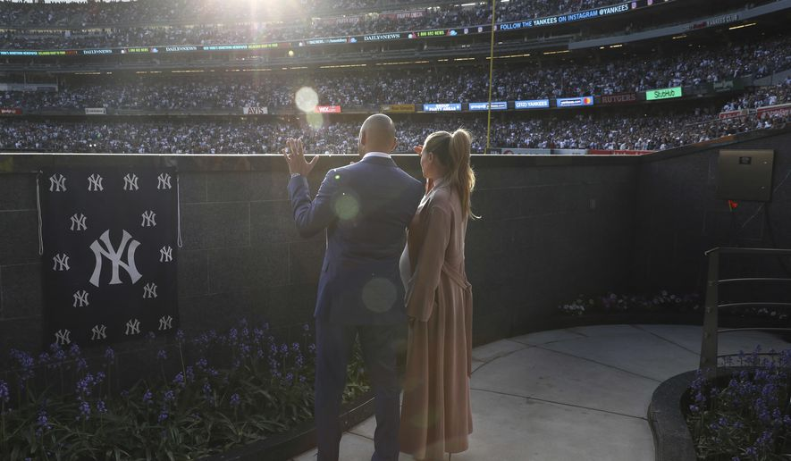 Former New York Yankee Derek Jeter waves to fans while standing with his wife Hannah Jeter during a ceremony to retire his number at Yankee Stadium in New York, Sunday, May 14, 2017. (AP Photo/Elsa Garrison, Pool)