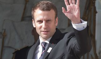 New French President Emmanuel Macron waves to the media after a meeting with the International Olympic Committee at the Elysee palace in Paris, France, May 16, 2017. France's new President Emmanuel Macron is hosting the International Olympic Committee to try to boost Paris' bid to beat out Los Angeles in the heated race for the 2024 Games. (AP Photo/Michel Euler)